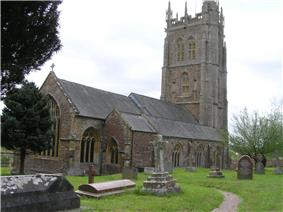 Gray stone building with ornate square tower and slate roof. In the foreground are gravestones.