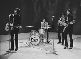 Four members of the band the Kinks stand onstage, during a television appearance. From left to right is Ray Davies, wearing a leather suit and long black pants. He is strumming an acoustic guitar and preparing to sing into a microphone placed in front of him. Next is Mick Avory, seated and playing the drums. He is wearing a bright coloured long sleeve shirt and dark pants. After him is bassist Pete Quaife, playing his instrument and wearing set of clothes similar to Avory's. Last is Dave Davies, wearing what appears to be a leather suit with a short tie, black pants and high-heeled loafers. He plays an elaborate v-shaped electric guitar and is standing behind a microphone.