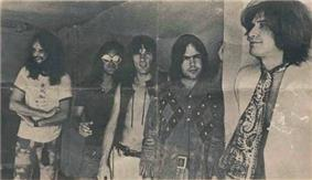 Five smiling men in a row, diagonal to camera angle. The man on the left (farthest to the back) has very long hair and a full beard; he wears a white T-shirt and tie-dyed pants. Next to him, Dave Davies, also with very long hair, wears reflective sunglasses, a black short-sleeved shirt, and jeans. In the middle, Mick Avory wears an unbuttoned leather vest and white pants. The man to his right wears a heavy, probably brown leather jacket with a design that is possibly Native American. On the far right, in front, Ray Davies wears a giant paisley kerchief knotted like a tie, over a white jacket.