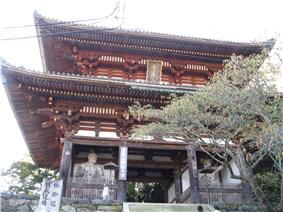 A two-storied wooden gate with white walls and faded red colored beams. There are two guardian statues in the side bays of the lower floor.