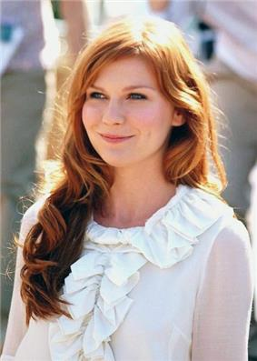 A red-headed woman smiles while wearing a white top with frill detailing.