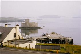A white building sits above a concrete pier. Offshore there is a small island on which there is a building with grey featureless walls. Various other islets can be seen in the background through the mist.