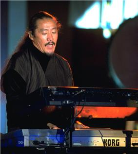 A man in black clothing behind a set of keyboard instruments