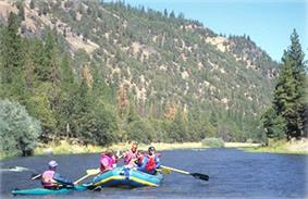 A total of five people, four in an inflatable raft and one in a kayak, floating down a calm section of blue water