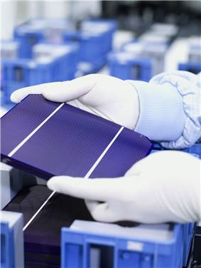 A part of gloved hands are hold a tablet-sized  solar cell with three panels.