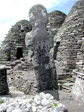 Three beehive shaped dry-stone huts surround a worn statue or cross