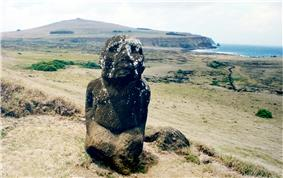 colour photo of kneeling figure carved from red stone, head splashed with white. A triangular hill is in the background and the sea in the top right