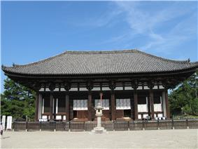 Wooden building with white walls and a trapezoidal roof.