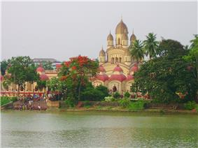 A temple with nine spires and few small temples surrounding it, with a waterbody in the foreground