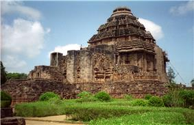 Picture of a square-shaped stone temple, with straight walls and a conical top. In front of the temple, stone structures are seen, as well as a green garden.