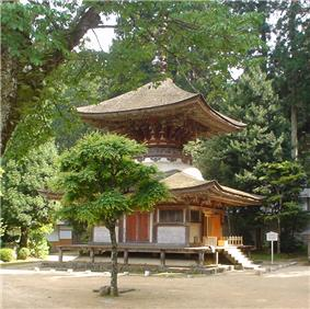A two-storied pagoda shaped tower with a square base and a round upper story. The walls are faded white and the beams faded red.