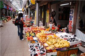 A female customer browsing a fruit shop. Banana and grapes are displayed on the front.