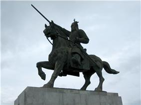 A bronze statue of a knight in armor on a riding horse against gloomy skies