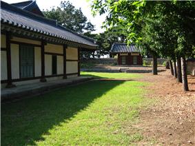On a sunny day, a Korean traditional wooden building painted with white and dark red stands on a grass field. Luxuriant trees are seen on the right while a gate is shown at a distance.