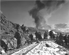 Soldiers watch a hill in front of them as aircraft drop bombs on it