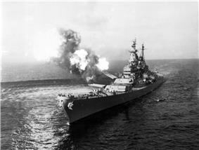 A black-and-white photograph depicting a large gunship sailing toward and slightly to the left of the camera. Guns of various size are visible on the ship, with smoke and flames visible from the turret No. 2 as the gun fires at an unseen target. The pressure from the gun fire has created a disturbance on the water surface.