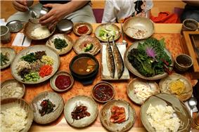 An array of about 10 small side dishes, a bean curd stew, and leaf vegetables on a table.