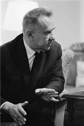 A man in a dark suit, seated, in discussion with someone to his left