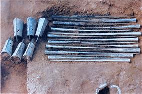 Pit with about ten long blue-green rusty metal sticks arranged parallel to each other and six bells.