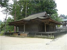 Wooden building with a hip-and-gable roof and step canopy. A shorter aisle is attached to the right side.