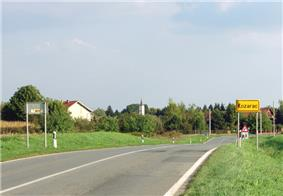 A view of a road from a side, showing two traffic lanes of a single carriageway as the road enters a village. A traffic sign indicating name of the village is visible on the right.