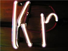 Illuminated white gas discharge tubes shaped as letters K and r