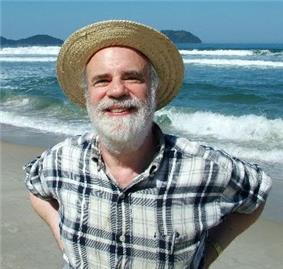 Man with a beard and straw hat on a beach