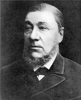 A man of around 50 with a dark suit and a dark chinstrap beard