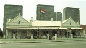 A Dutch colonial-style house with the flag of the South African Republic flying outside.