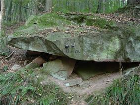 Photo shows two cannonballs embedded in a large boulder in a forest. Engraved in the stone is
