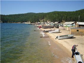 A sandy beach showing cabins and boats drawn up on the shore
