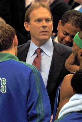 A man, wearing a black suit, blue shirt and red tie, is standing in the middle of a huddle.