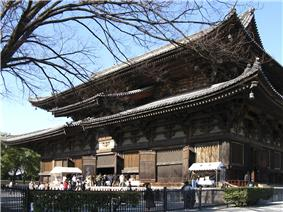 Large wooden building with a hip-and-gable roof and enclosing pent roof.
