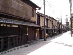 Wooden two-storied houses lining a small street. The upper stories' windows are covered.