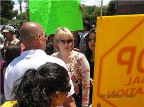 A woman in her thirties with fairly short blond hair, wearing sunglasses and a beige and pink top, is surrounded by a crowd.