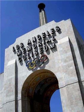 Photograph of the peristyle gate of the Los Angeles Memorial Coliseum, tile mosaicon the underside of the arch, and the Olympic torch reaching to the blue sky.