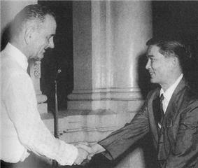 Tall Caucasian man standing in profile at left in a white suit and tie shakes hands with a smaller black-haired Asian man in a white shirt, dark suit and tie.