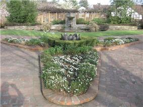 Photograph of a formal garden at the Luther Burbank House and Gardens, featuring brick walkways and planterboxes, a small lawn, a fountain and pool, low stone walls, and wooden trellises.