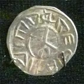 A small silver coin depicting a cross