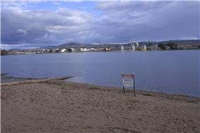 A metal sign erected on the sandy shores of the lake advises of the ban on water activity due to pollution