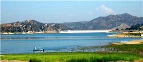 A light blue, broad lake is formed by a dam seen in the distance in a wide valley between arid hills