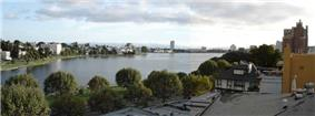 Panoramic photograph of the Lake Merritt Wild Duck Refuge, surrounded by the buildings of Oakland.