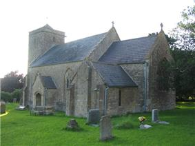 Gray stone building with square tower at left hand end. In the foreground are gravestones on grass.