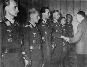 Six men all wearing military uniforms and decorations standing in row. The third man from the far right is shaking hands with another man.