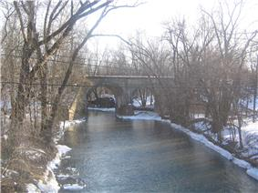 A winter view of a stream with snow on the banks. A stone and concrete railroad bridge appears near the center of the photo, crossing the stream. The trees are bare and power lines appear near the center of the photo as well.