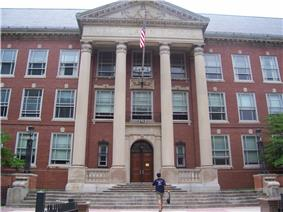 Three-story brick building façade with three white columns surrounding a brown wooden door located on the ground floor
