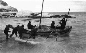 A group of men pushing a boat from a rock beach into the sea, with a background of rocks.