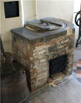 Photograph of a brick-lined laundry copper, with a round lid in the top and a grate below for the fire