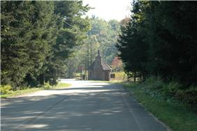 A road through a forest leads to a fieldstone building with a chmney and steep roof next to a stop sign