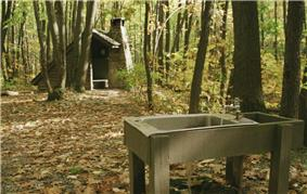 A metal sink with running water supported by wooden beams in the foreground, a wooden open shelter with a stone chimney amidst the trees in the background